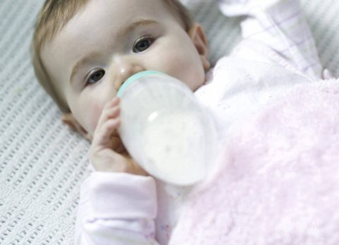baby drinking bottle of formula milk