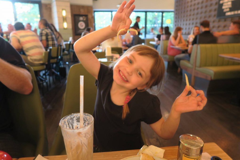 little girl happy in local restaurant with chips maidstone