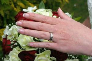 woman's hand with wedding ring over flowers